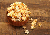 Popcorn in brown bowl on wooden table — Stock Photo