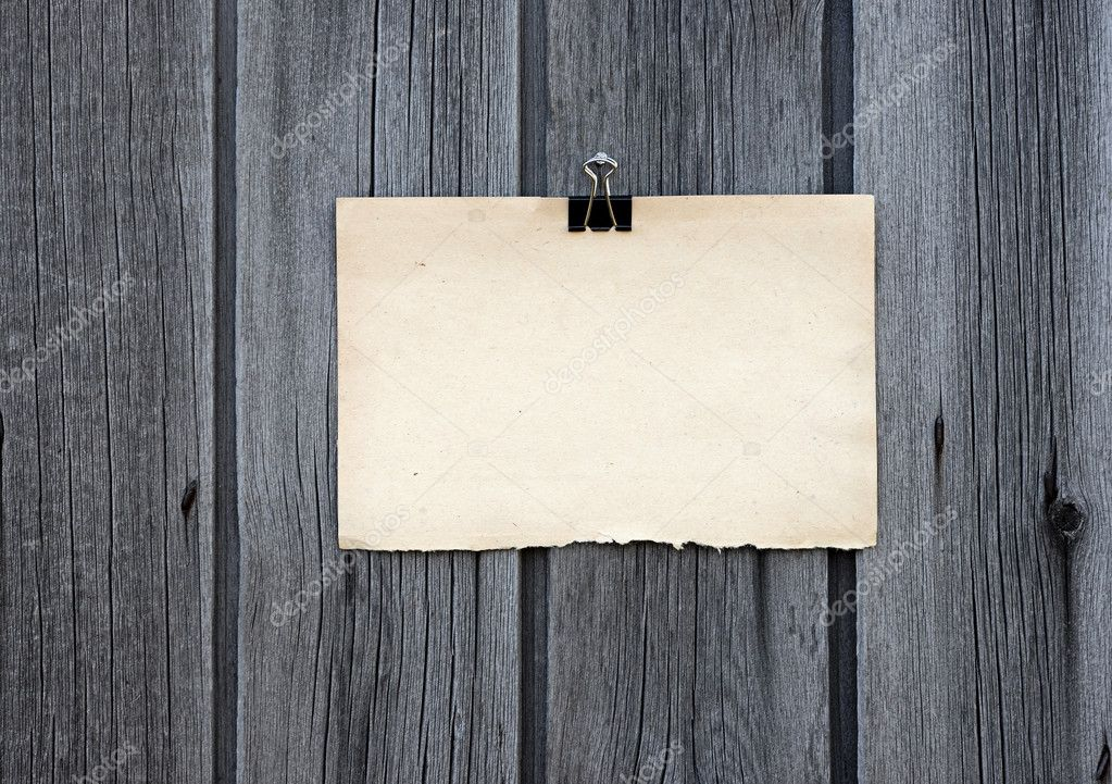 Black clip and old blank note paper hang on wood panel — Stock Photo #11561435
