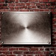 Rusty metal plate on old brick wall texture — Stock Photo