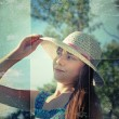 Stock Photo: Lonely girl in a white hat looks into the distance. Photo in old