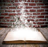 An open book with letters falling into the pages — Stock Photo