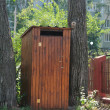 Stock Photo: Small wooden outdoors toilet in summer.