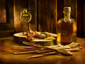 Oil and herbs in an antique setting — Stock Photo