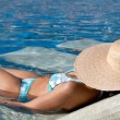Young Woman Sunbathing in the Pool - Stock Photo