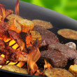 Flames grilling steaks and vegetables — Stockfoto #11059133