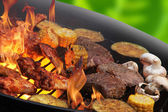 Lågorna grillning en biff och grönsaker — Stockfoto