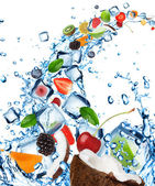 Fresh fruit in water splash with ice cubes — Stock Photo