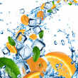 Fresh oranges in water splash with ice cubes — Stock Photo
