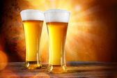 Beer in a glass with gold background — Stock Photo