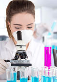 Female researcher with test tubes in laboratory — Stock Photo