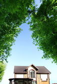 Beautiful house under the arch of trees — Stock Photo