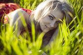 Beautiful girl lies in a green grass — Stock Photo
