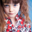 Beautiful little girl on a blue background — Stockfoto
