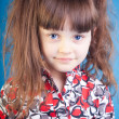 Beautiful little girl on a blue background — Foto de Stock