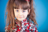 Beautiful little girl on a blue background — Stock Photo