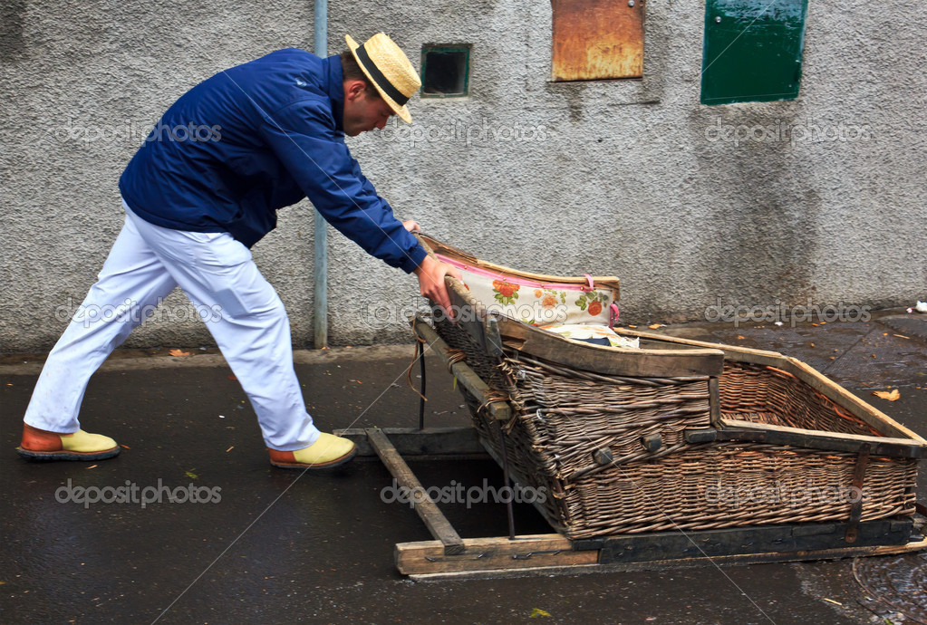 Monte, Portugal - May 02, 2012 Leader of the toboggan, the typical Madeira sled baskets in Monte - Madeira (Portugal). One push а leader downhill transport cage. This is done on public streets and is an old tradition. — Stock Photo #11217729