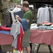 Man Holding Clothes at Sale — Photo