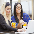 Stock Photo: Girls in restaurant with laptop