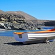 Boat in a black sand beach in Fuerteventura, Spain — Stock Photo