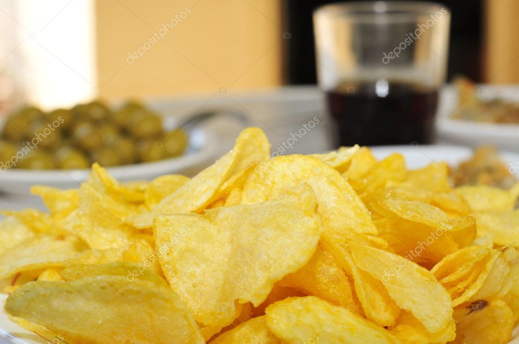 Closeup of a plate whit potato chips on a table with other appetizers, as olives  Stock Photo #11993797