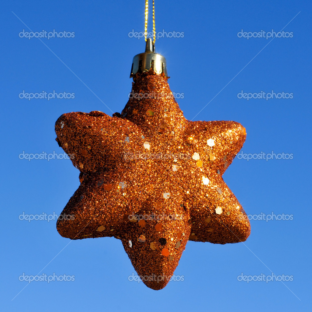 A golden christmas star hanging on a blue background — Stok fotoğraf #12007872