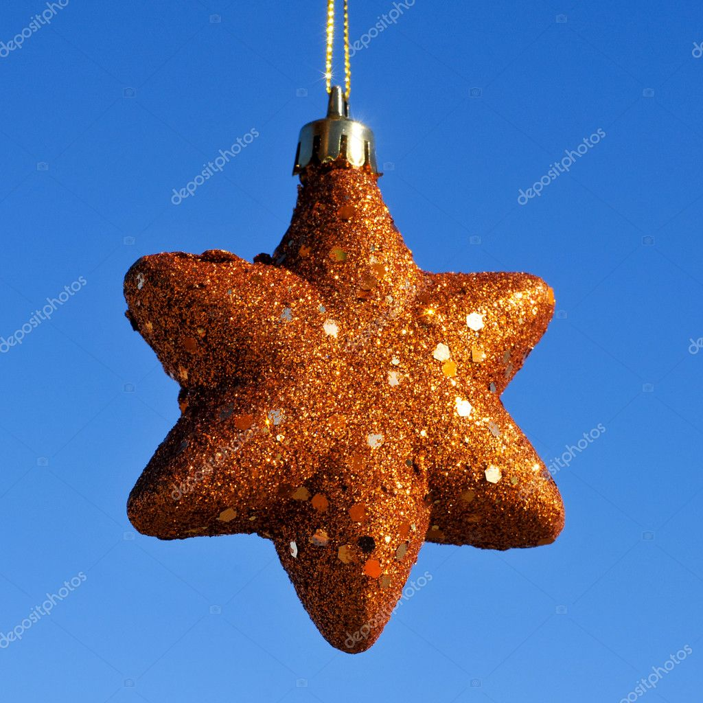 A golden christmas star hanging on a blue background — Zdjęcie stockowe #12007872