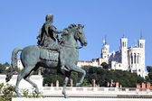 Famous statue of Louis XIV and Basilique Fourviere — Stock Photo