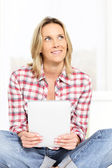 Woman on sofa with tablet — Stock Photo