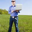 Royalty-Free Stock Photo: Businessmanon meadow, with a laptop