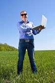 Businessmanon meadow, with a laptop — Stock Photo