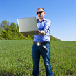 Businessmanon meadow, with a laptop — Stock Photo #10965733