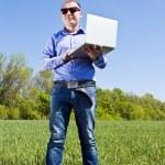 businessmanon 草甸,用一台笔记本电脑 — 图库照片