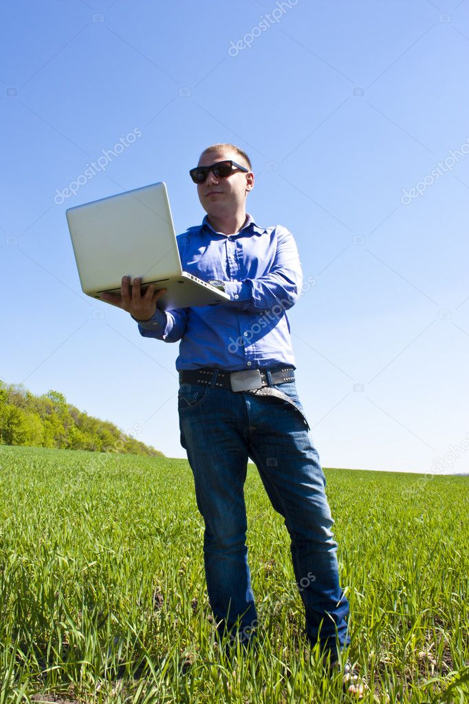 Happy young businessman, on spring field — Stock Photo #10965729