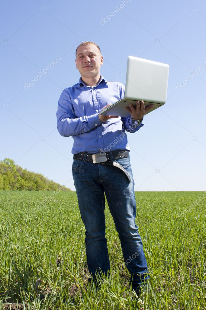 Happy young businessman, on spring field — Stock Photo #10965731