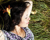 Adult woman resting on a green field — Stock Photo
