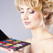 Beautiful young blond, holding eye shadow palette — Stock Photo