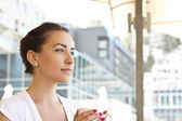 Young woman drinking coffe in a cafe outdoors — Stock Photo