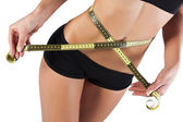 Thin young woman measures the waist — Stock Photo