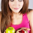 Woman with apple and cake in hands — Stock Photo