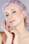 Beautiful young woman, with perforation lines on her face before plastic surgery operation — Stock Photo