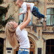 Happy young woman lifting her son high up — Stock Photo