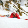 Cute young female skier looking at the camera after falling down on mountain slope — Stock Photo
