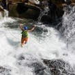Young man rope jumping in rapid waters of a mountainous river — Stock Photo #11856381