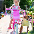Cute four-year old girl on a bicycle with staffordshire terrier — Stockfoto