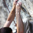 Closeup view of a rock climber's hands on a cliff - 图库照片