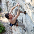 Stock Photo: Rock climber focusing on next movement