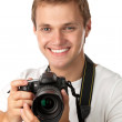 Portrait of a handsome young man holding a camera — Stock Photo