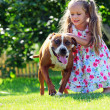 Cute little girl playing with her Staffordshire terrier dog — Stock Photo