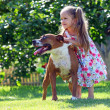 Cute four-year old girl playing with her dog — Photo