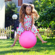 Cute four-year girl bouncing on big ball outdoors — Stock Photo #11856703
